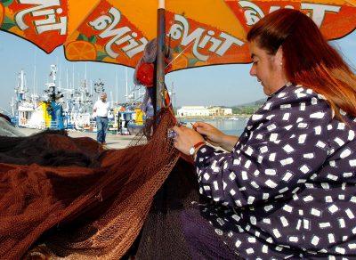 Una mujer cose redes en el puerto de Santoña (Cantabria). EFE/Esteban Cobo